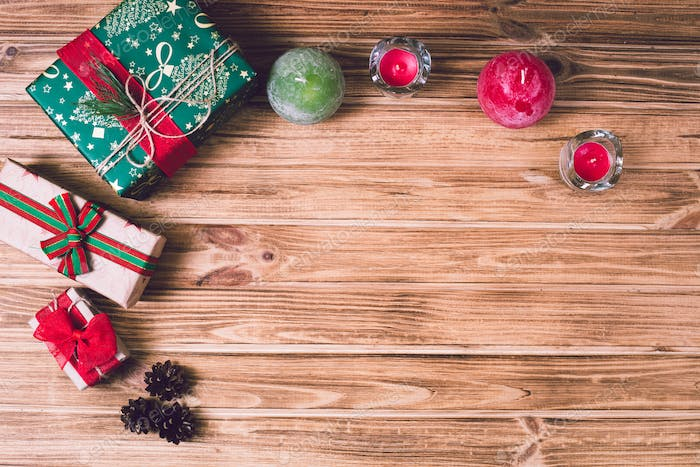 Christmas holiday gift box on decorated festive table with pine cones on wooden background