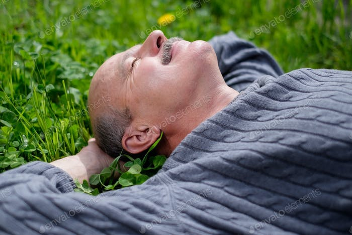 Mature Happy Man Lying On Green Grass. He holds onion leaf in mouth and closes eyes.