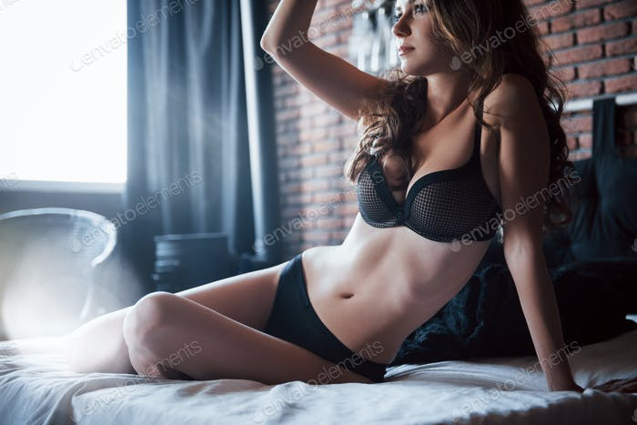 An attractive lady in the bedroom. Good morning rest at home. The girl in black lingerie