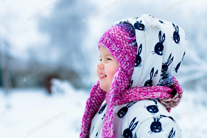 Child in snowy day. Baby girl in white snowsuite and pink hatin the snow winter park.  Happy. Smile.