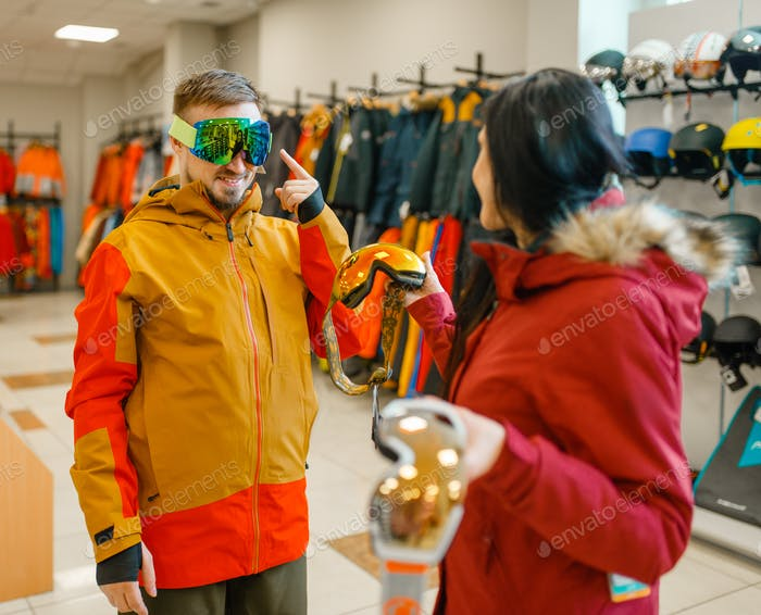 Couple trying on mask for ski or snowboarding