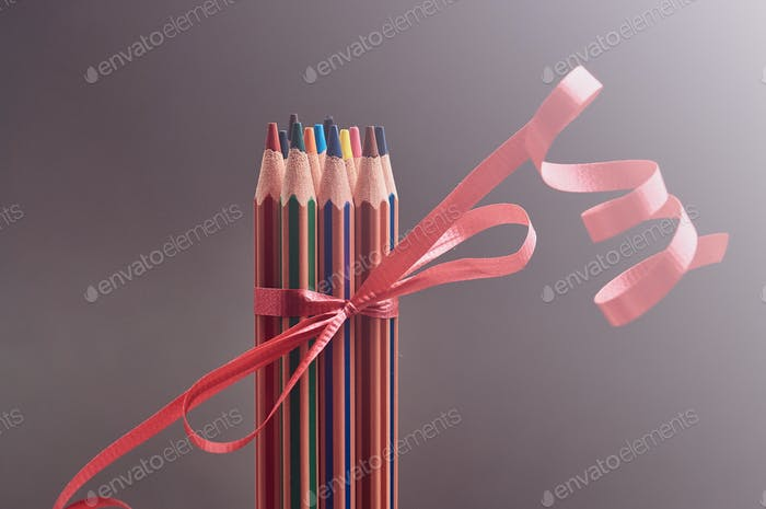 Group of multicolored pencils decorated with red gift ribbon.