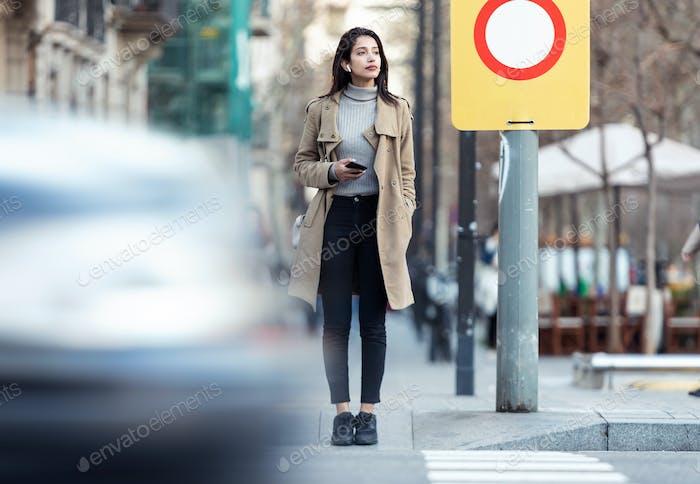 Hübsche junge Frau, die die Straße überquert, während Musik mit den drahtlosen Ohrhörern hören.