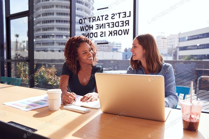 Two Businesswomen With Laptop At Desk By Window In Office Collaborating On Project Together