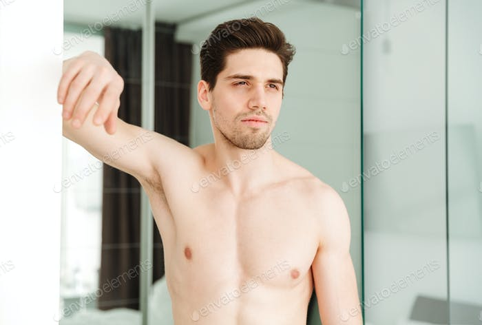 Serious naked man standing in home