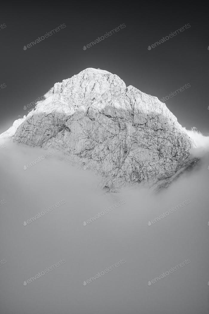 Berggipfel über Wolken. Schwarz-Weiß-Monochrome Schöne Kunst