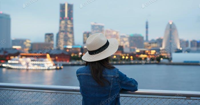 La mujer mira alrededor en la ciudad de Yokohama