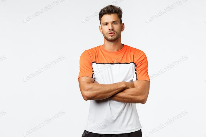 Fitness trainer disappointed client missed training. Handsome strong and masculine man, football