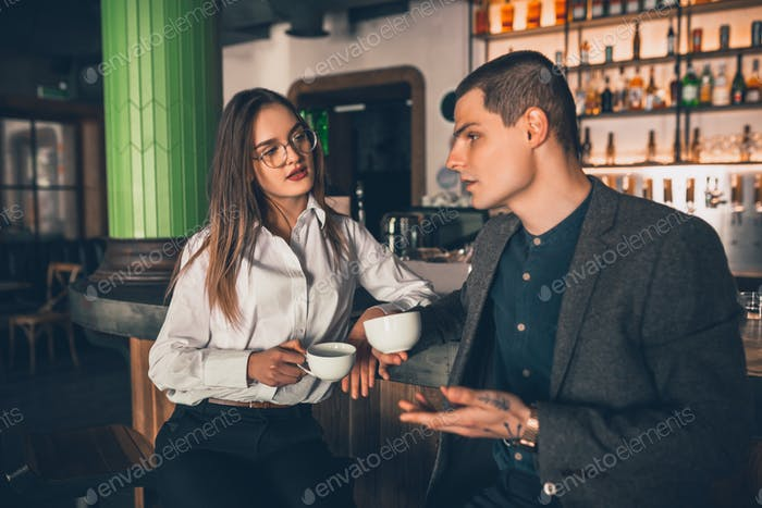 Cheerful man and woman talking, enjoying a coffee at the coffee shop, cafe, bar