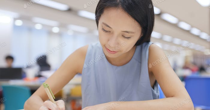 Woman working on her homework in library at university campus