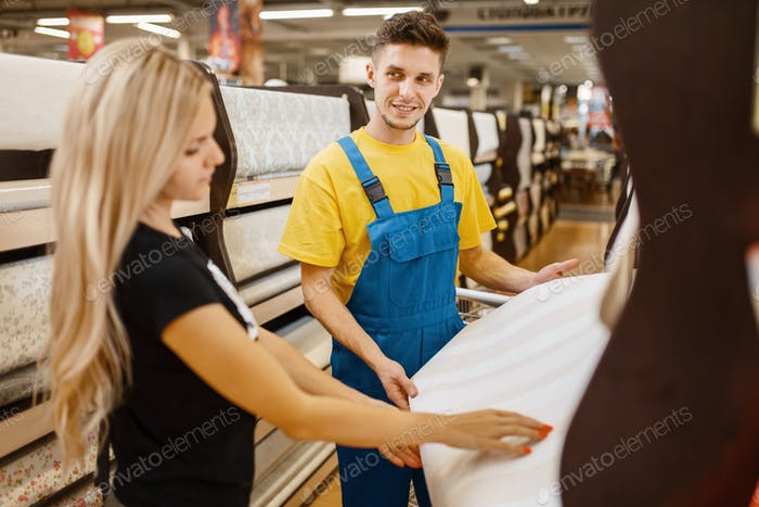 Assistant and female customer choosing wallpapers