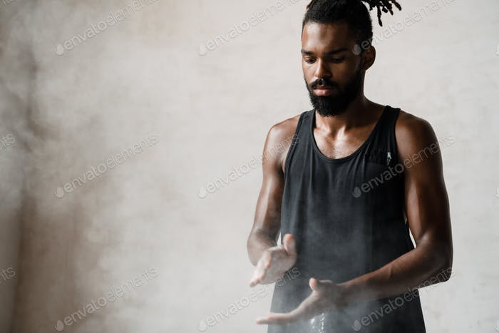 Image of african american sportsman clapping hands with talcum powder