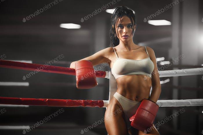 Boxeador femenino apoyado en la cuerda