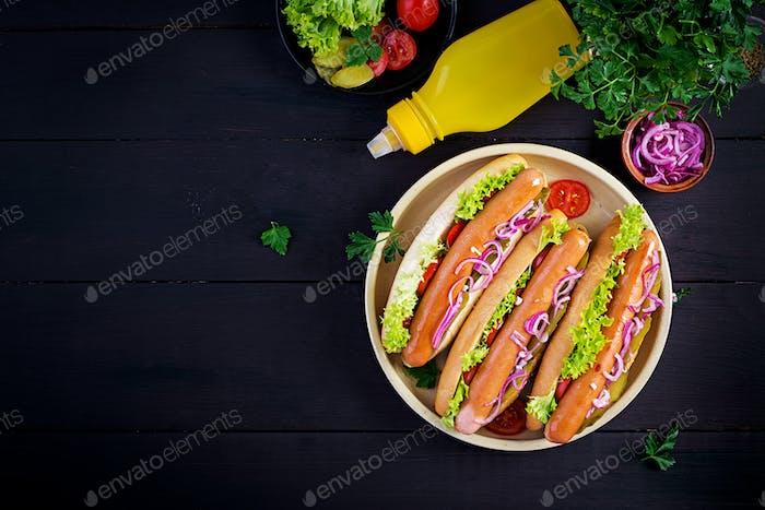 Hot Dog mit Wurst, eingelegte Gurke, Tomaten, roten Zwiebeln und Salat