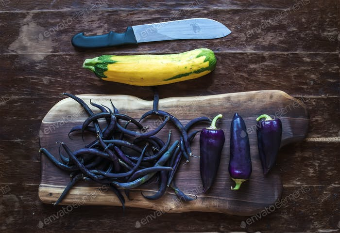 Violet chili peppers, beans and yellow zucchini