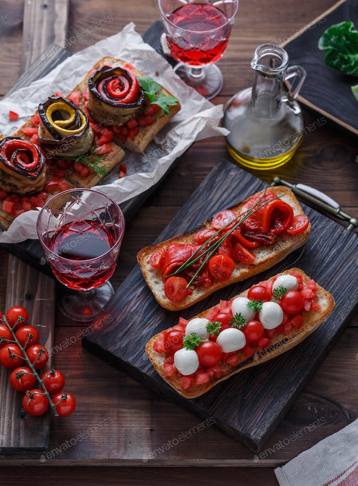 Bruschetta with tomato, basil and mozzarella cheese on wooden board. Traditional italian appetizer
