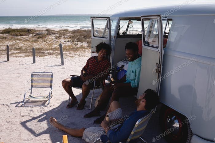 Front view of happy young multi ethnic men relaxing near camper van at beach in the sunshine