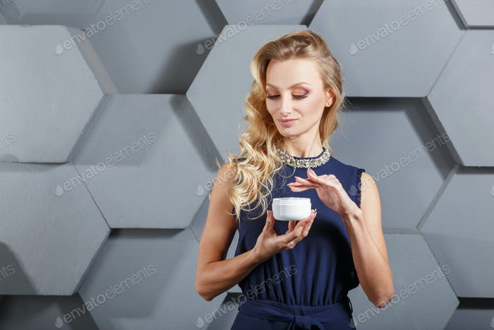 Beautiful blonde woman with clear skin and blue eyes keep on hands white jar with cream.