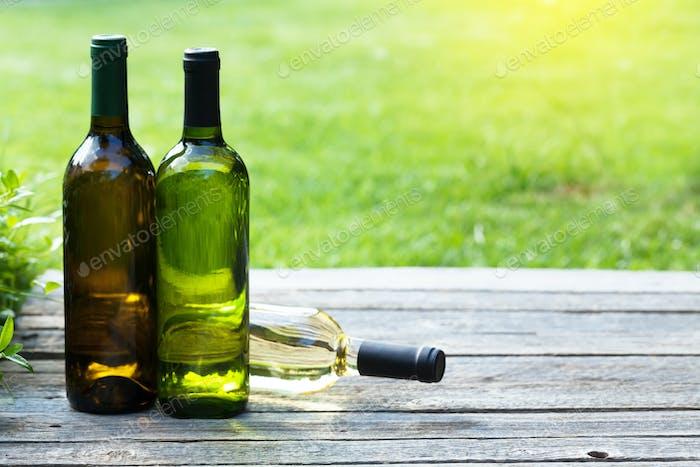White wine bottles on wooden table