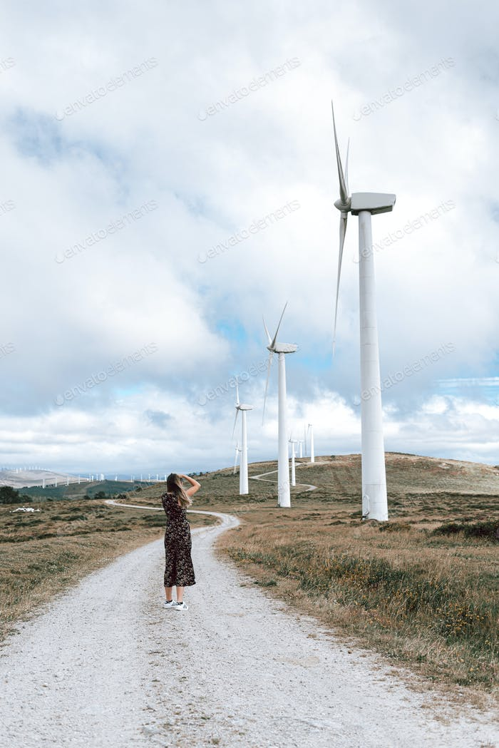 Mujer tomando Fotos en un parque de turbinas eólicas