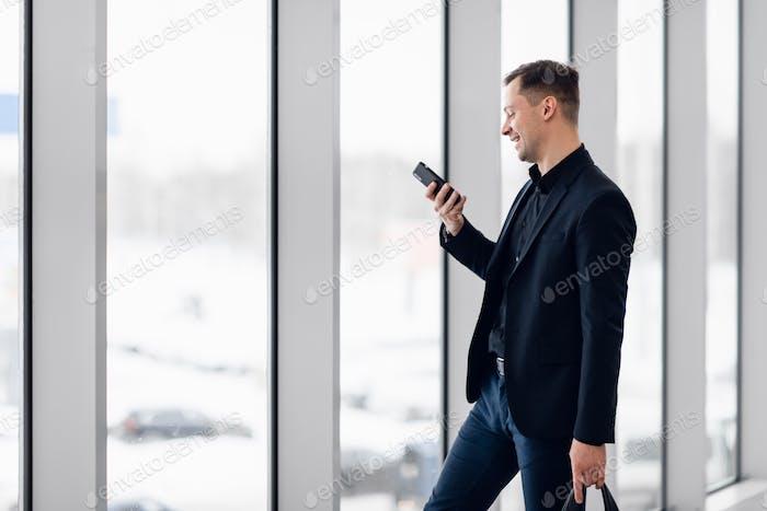 Концентрированный бизнесмен записывает голосовое сообщение в аэропорту