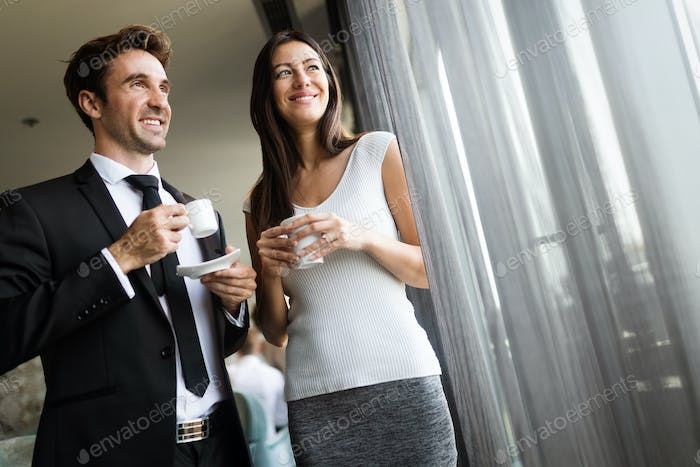 Portrait of pretty businesswoman drinking coffee, talking to male colleague