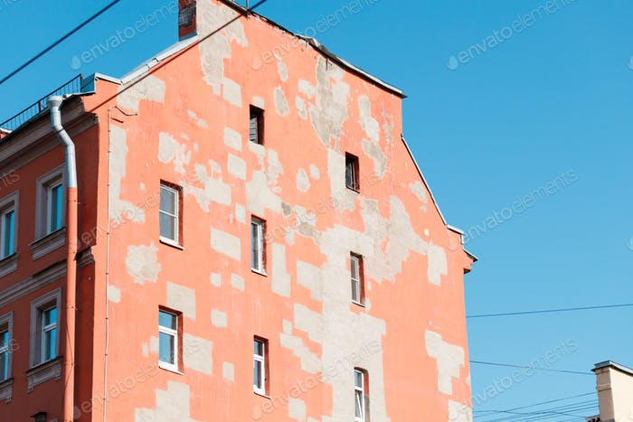 Old house of European city. Wall of pastel color with restoration spots.