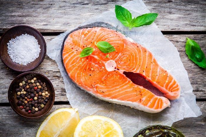 fresh raw salmon steak with salt, lemon, and basil
