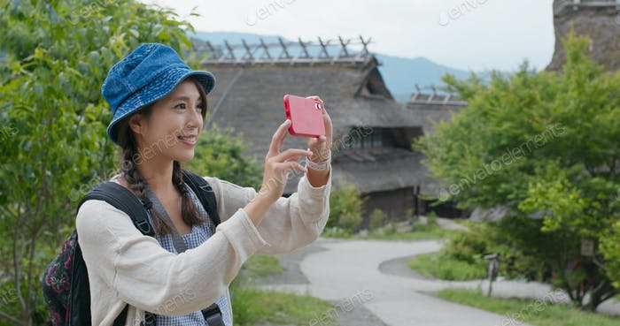 Woman use of mobile phone to take photo in Japanese wooden house