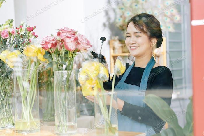 Florist spraying flowers in shop