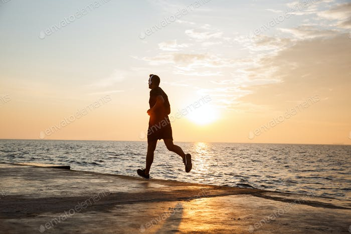 Image of muscular sporty man 30s in shorts and t-shirt running a