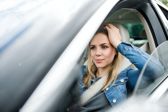 Young woman driver sitting in car, waiting.