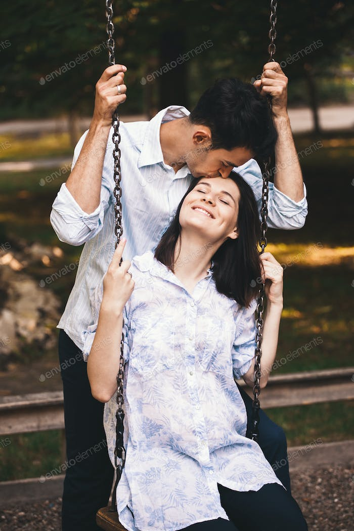 Smiling couple in love on a swing outdoors.