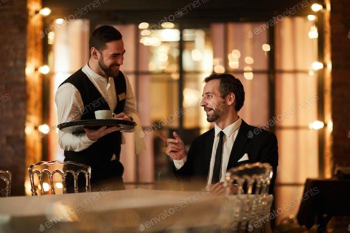 Smiling Businessman ordering Coffee in Restaurant
