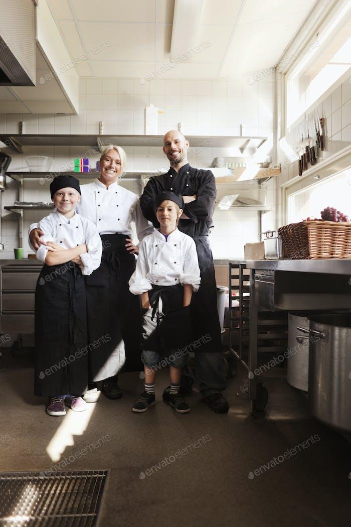Retrato da família chef em pé na cozinha do restaurante