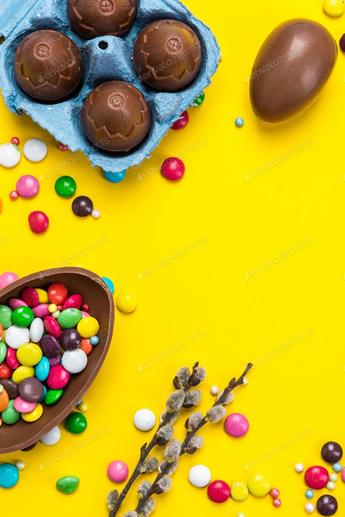 Colorful Easter BAckground. Chocolate Eggs and Candy on Yellow Background.