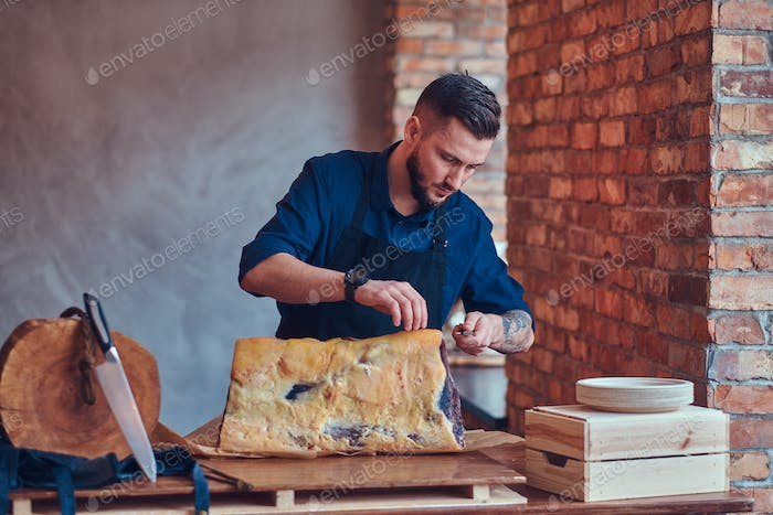 Professional butcher is cutting raw smoked meat on a table for c