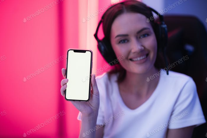 Happy gamer girl wearing headset showing smart phone display and pointing at blank screen with her