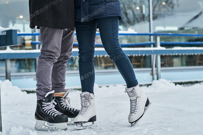 Happy couple dating in the ice rink, hugging and enjoying winter time