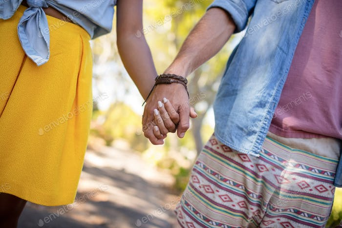 Mid section of couple holding hands in park