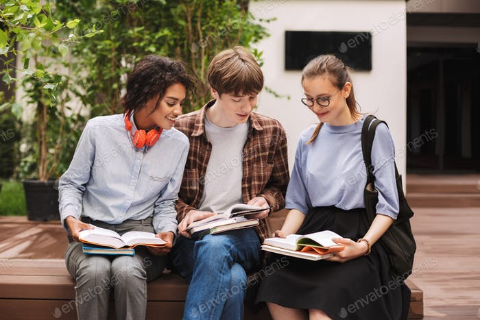 Group of smiling students sitting on bench and reading books in courtyard of university