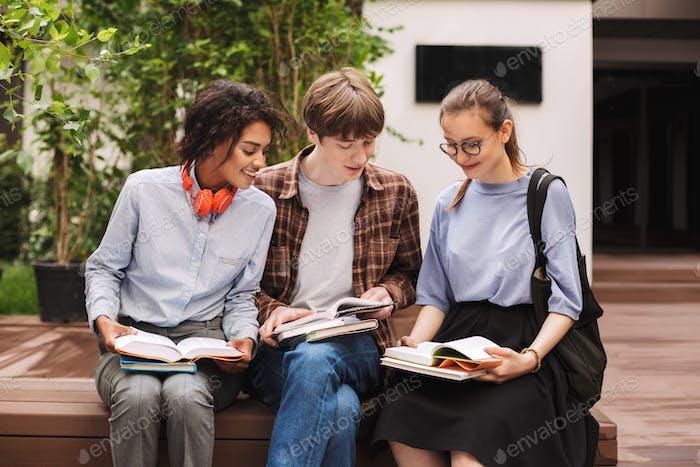 Grupo de estudiantes sonrientes sentados en el banco y leyendo libros en el patio de la universidad