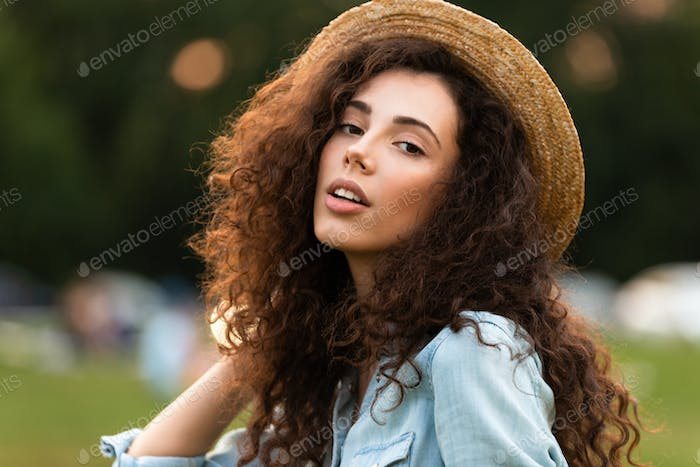 Image of pleased woman 20s wearing straw hat smiling, while walk
