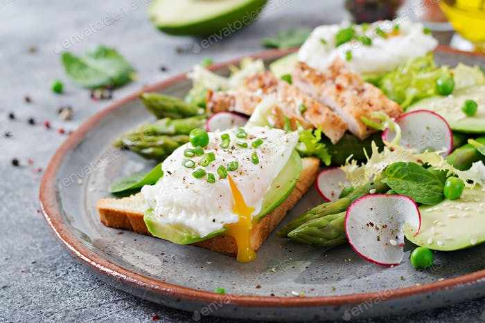 Healthy breakfast. Eggs poached on toast with avocado, asparagus and chicken fillet on grill.