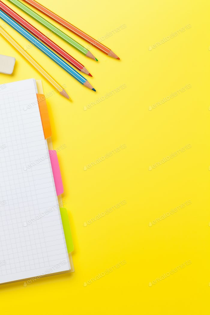 Office yellow backdrop with notepad and pencils