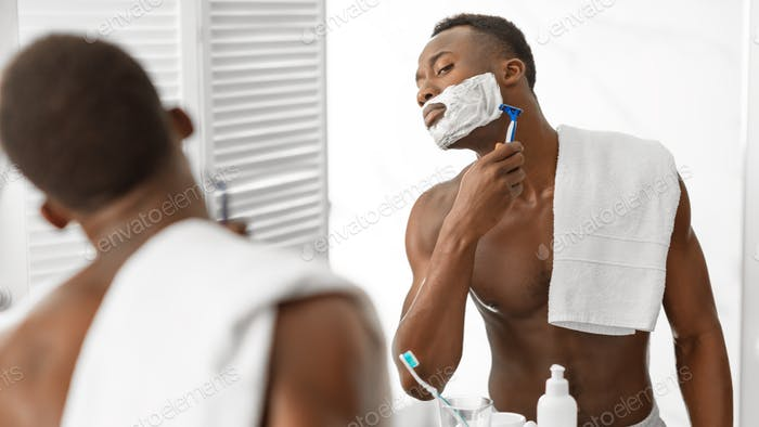 African Guy Shaving Face Covered With Shave Foam In Bathroom