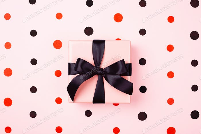 Pink Gift Box with Black Bow on Pink Background with Confetti.
