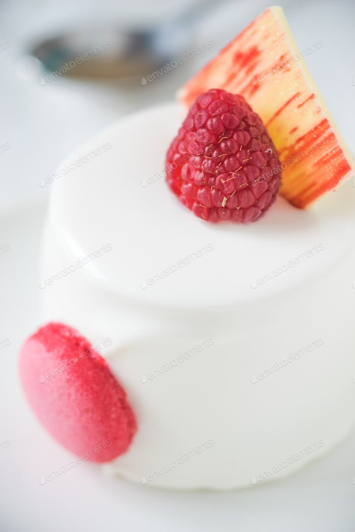 White cake with raspberry vertical