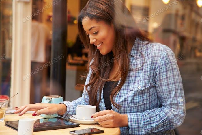Frau gesehen durch Fenster von Caf' mit digitalem Tablet