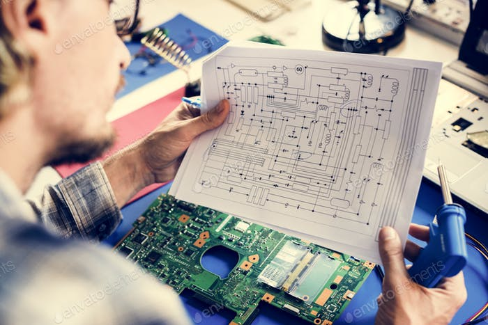 Technician studying electronics circuit guideline paper